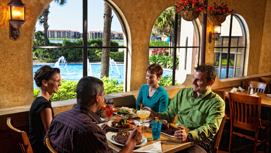 A Pair Of Couples Enjoying Dinner Together At Westgate Lakes Resort & Spa