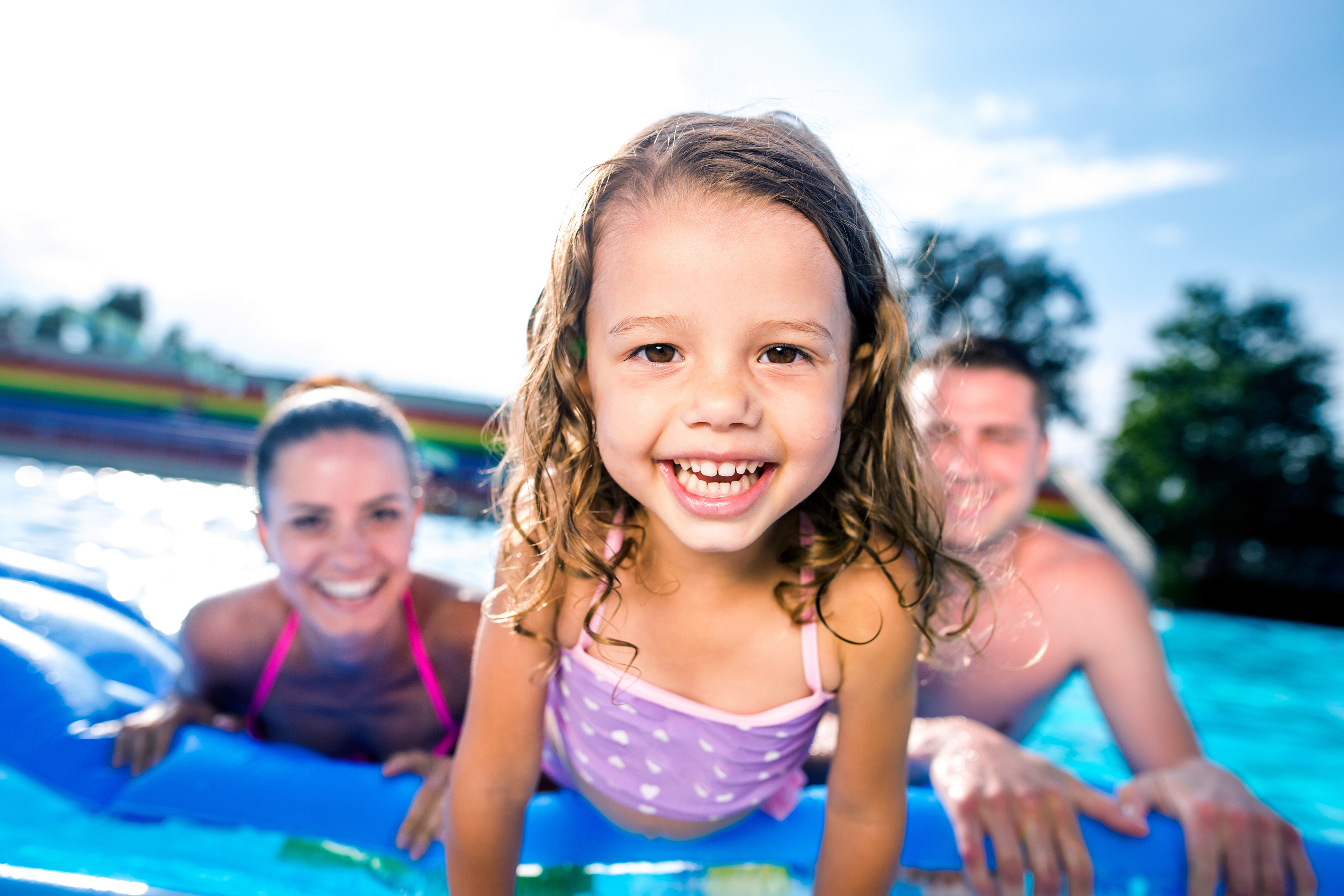 A little girl smiling while playing in the pool - Westgate Resorts