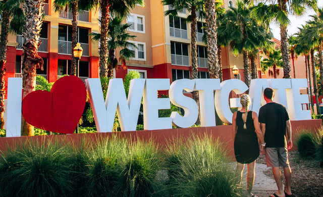 Couple Holding Hands In Front Of I Heart Westgate Sign