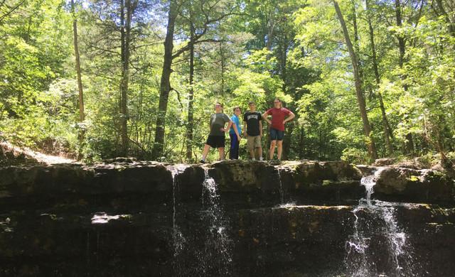 Kids standing on rocks by waterfall | Westgate Branson Woods Resort