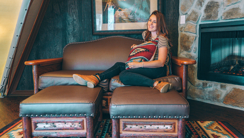 Girl sitting in the living area inside a Luxe Teepee Room for Glamping | Westgate River Ranch Resort & Rodeo | Westgate Resorts