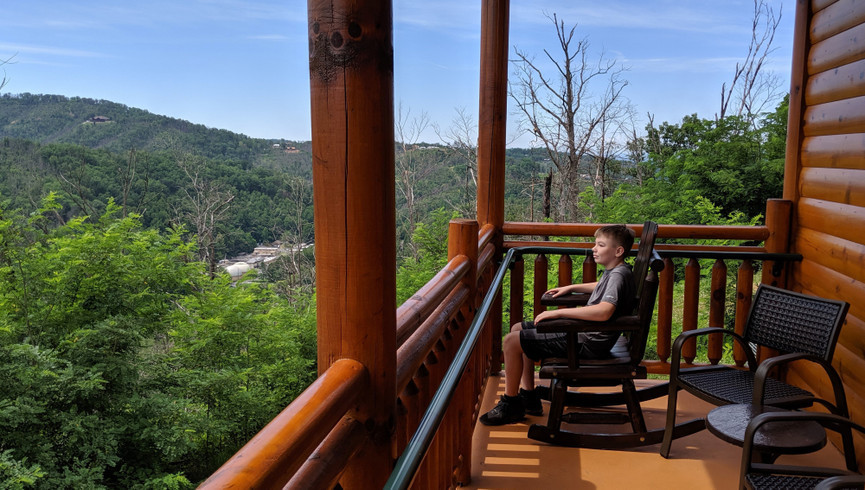 Child sitting in a rocking chair on balcony overlooking the Gatlinburg Smoky Mountains - Westgate Smoky Mountain Resort