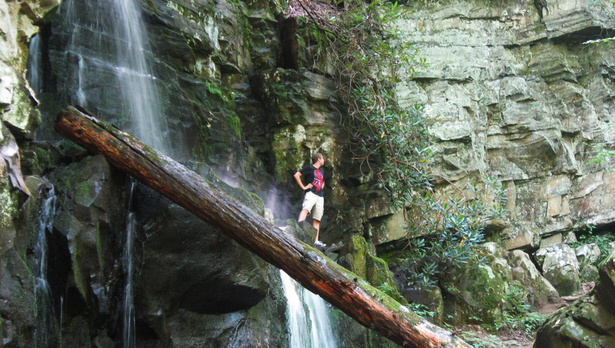 man posing on a log by a waterfall - Westgate Smoky Mountain Resort
