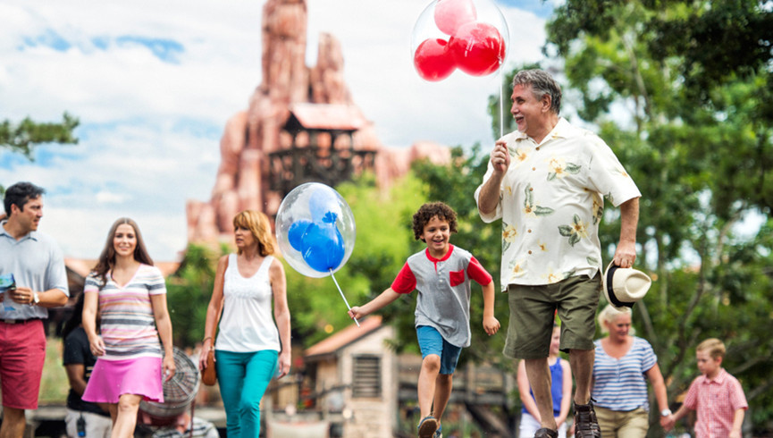 Grandfather And Grandson Holding Balloons Together At Disney World