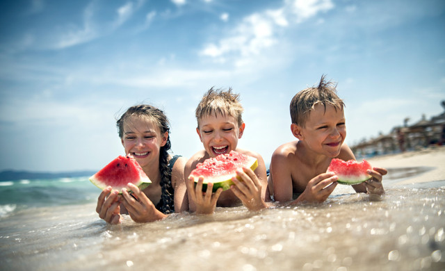 Three Children Eating Watermelon At The Beach