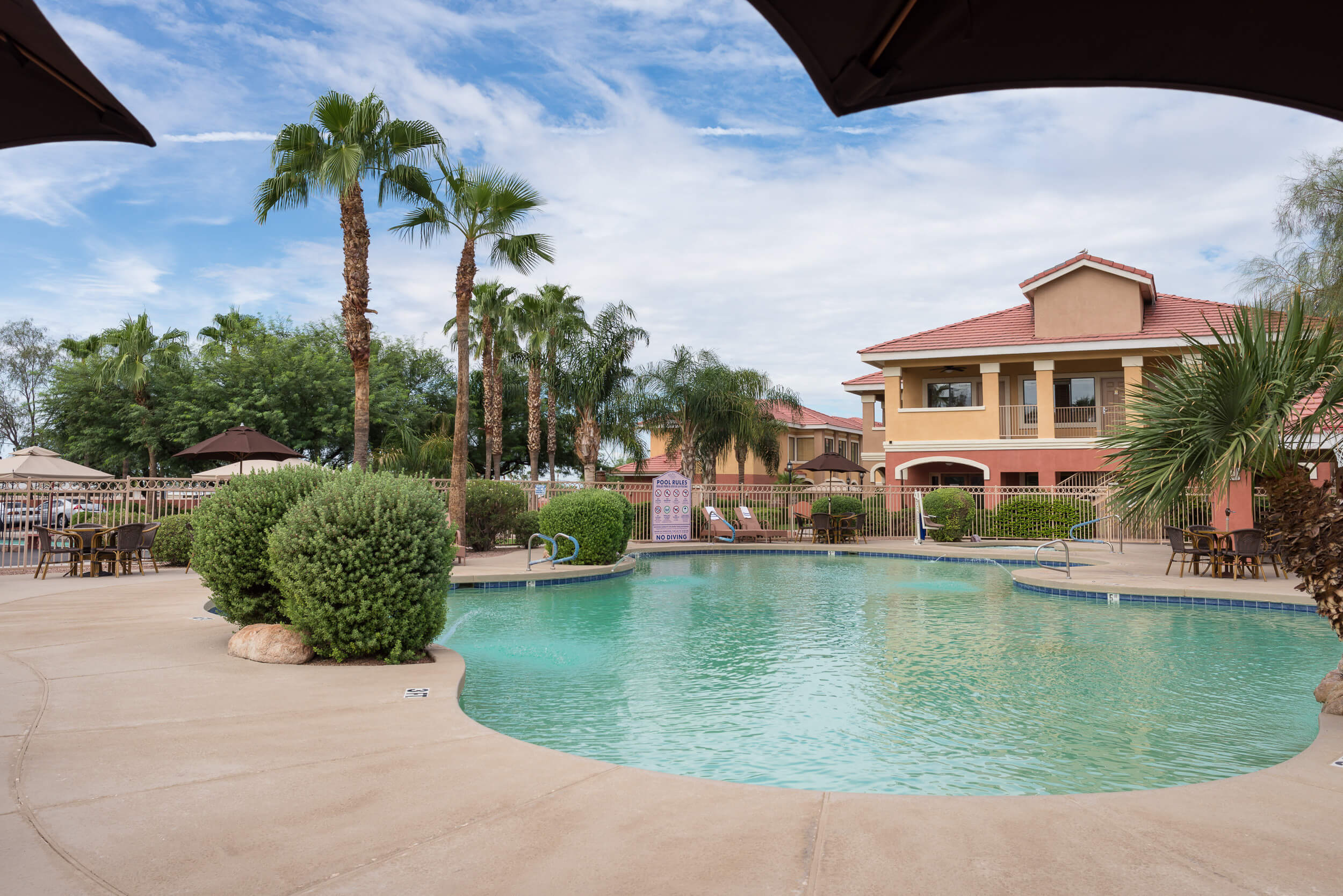 Heated outdoor pool surrounded by tables with umbrellas | Westgate Painted Mountain Golf Resort