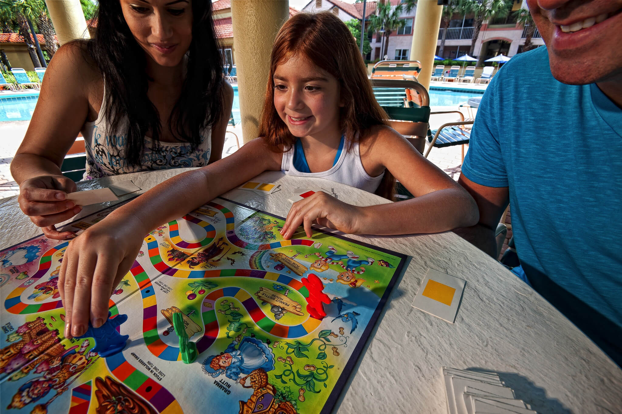 Mother, Father and daughter playing board game on pool deck | Westgate Blue Tree Resort