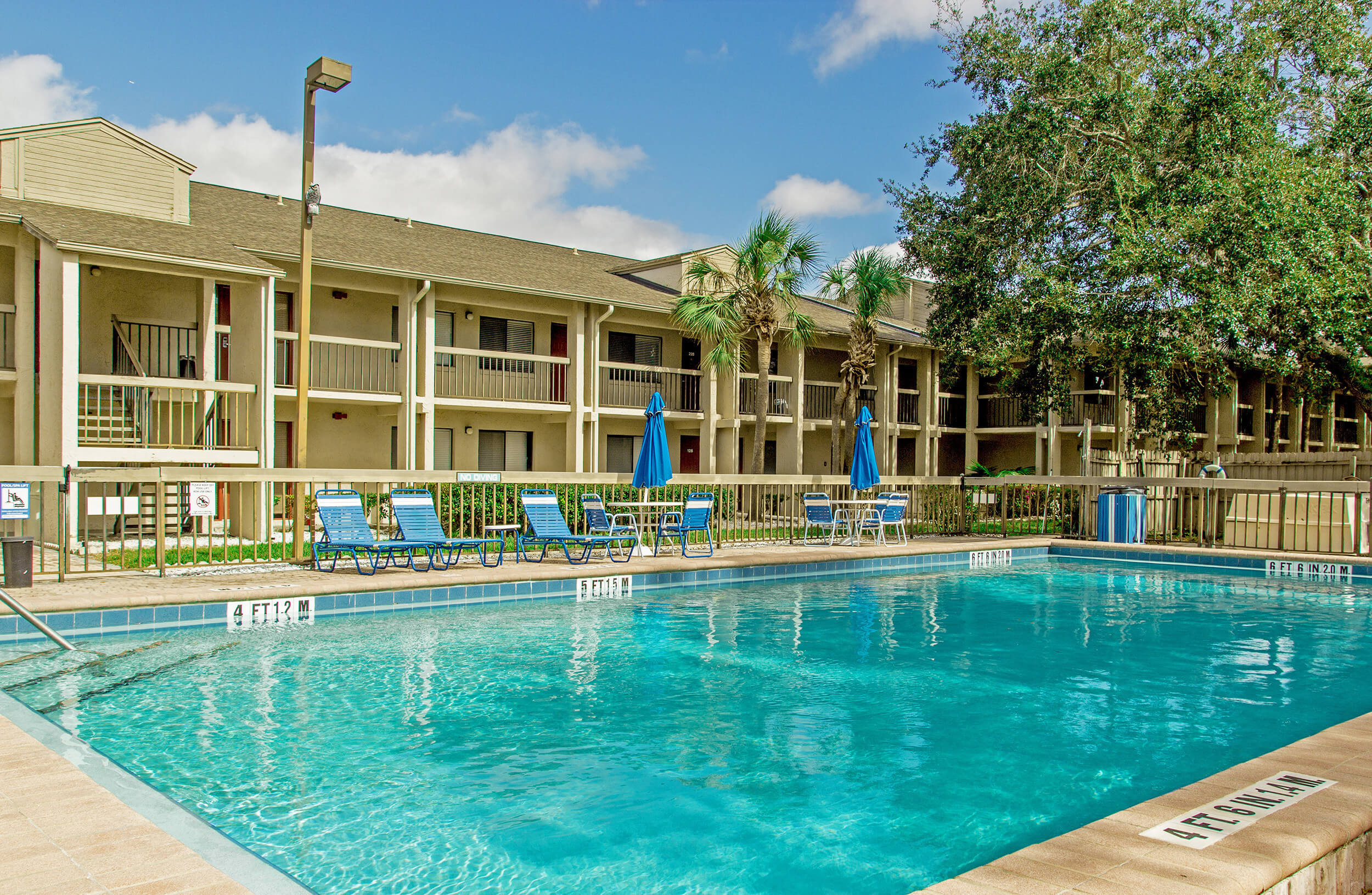 Club Orlando pool with lounge chairs, tables and umbrellas for shade | Club Orlando | Westgate Resorts