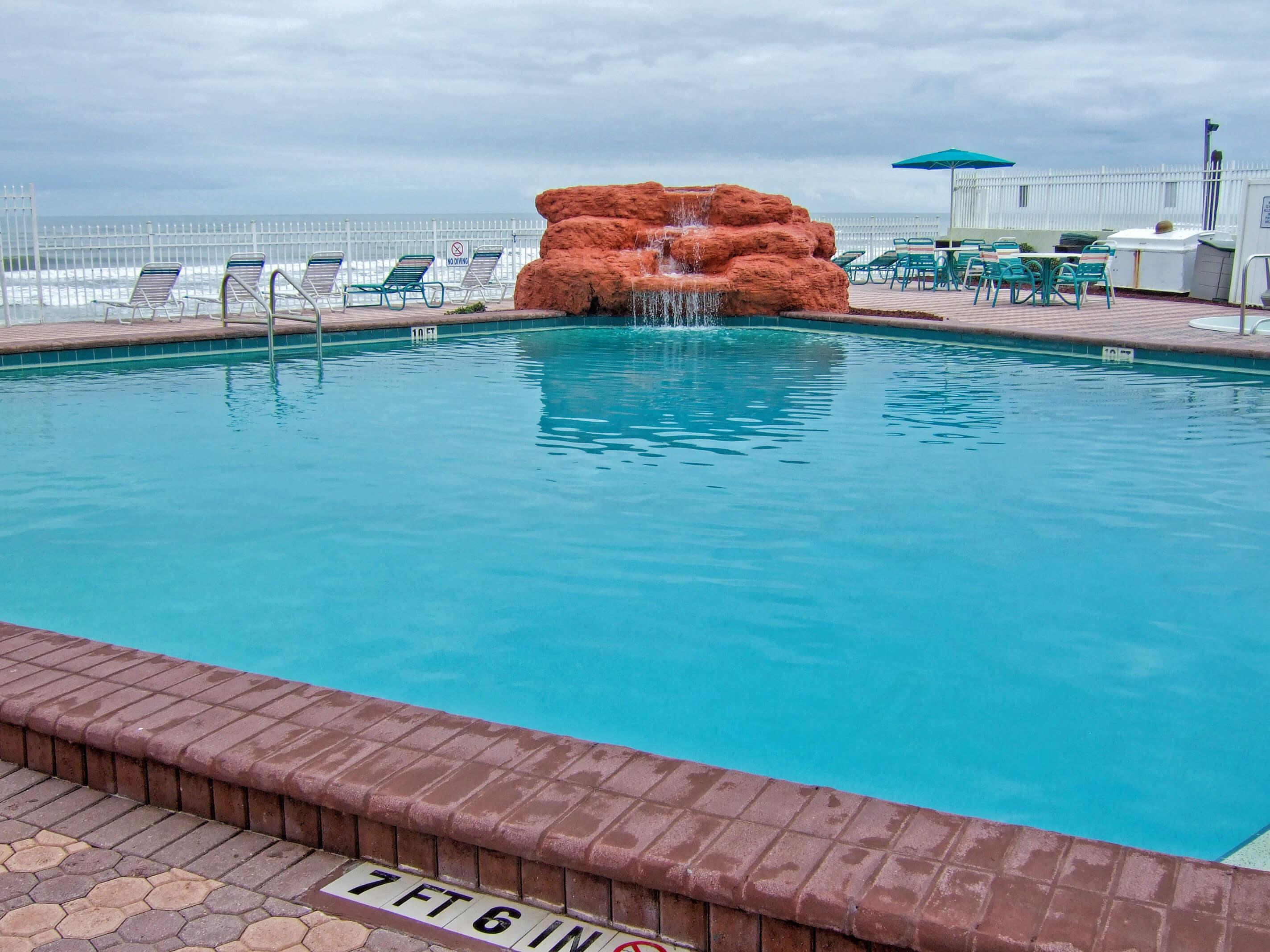 Heated outdoor pool with waterfall overlooking ocean | Harbour Beach Resort | Westgate Resorts in Daytona Beach FL