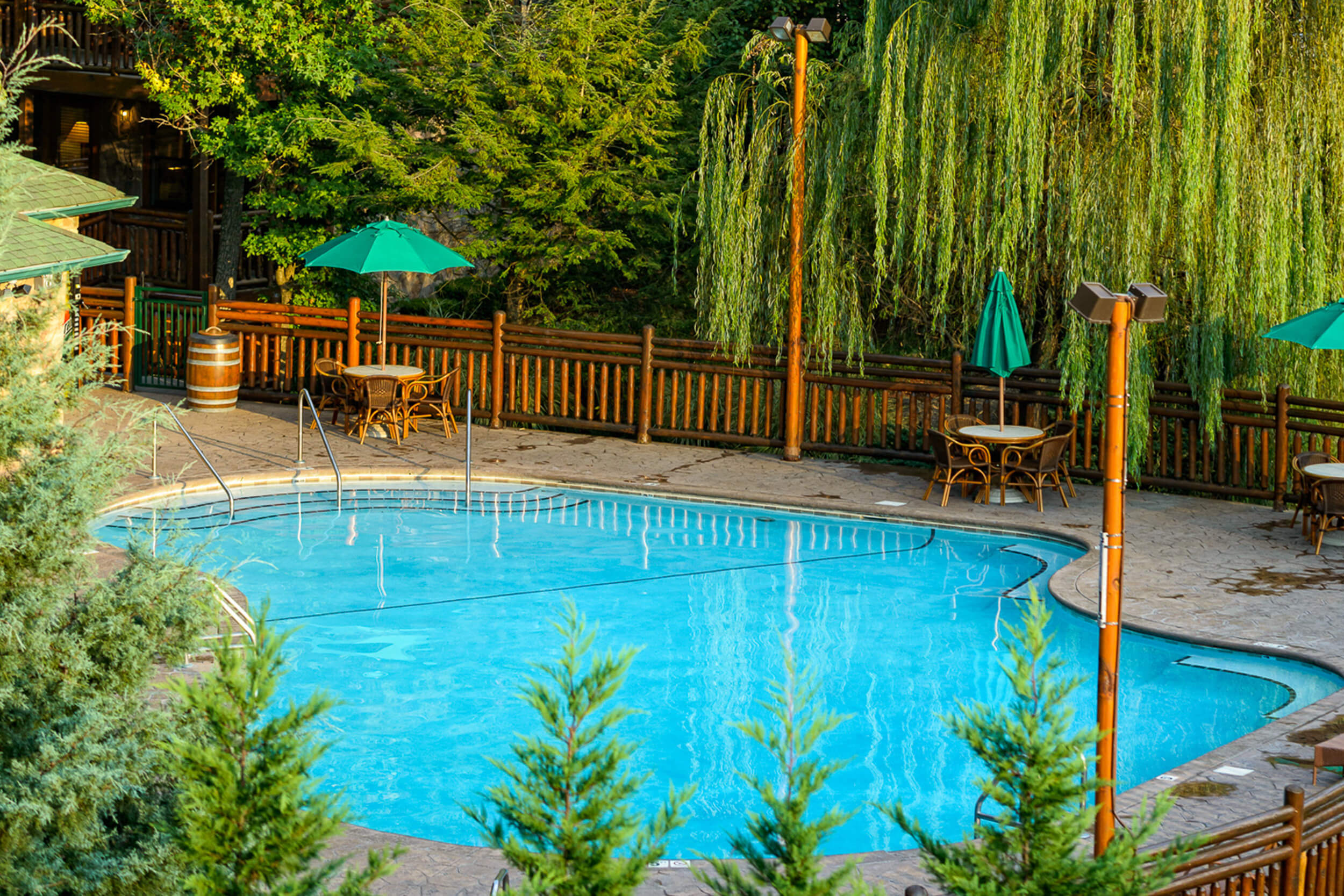 Outdoor pool with tables, chairs and umbrellas | Westgate Smoky Mountain Resort & Spa