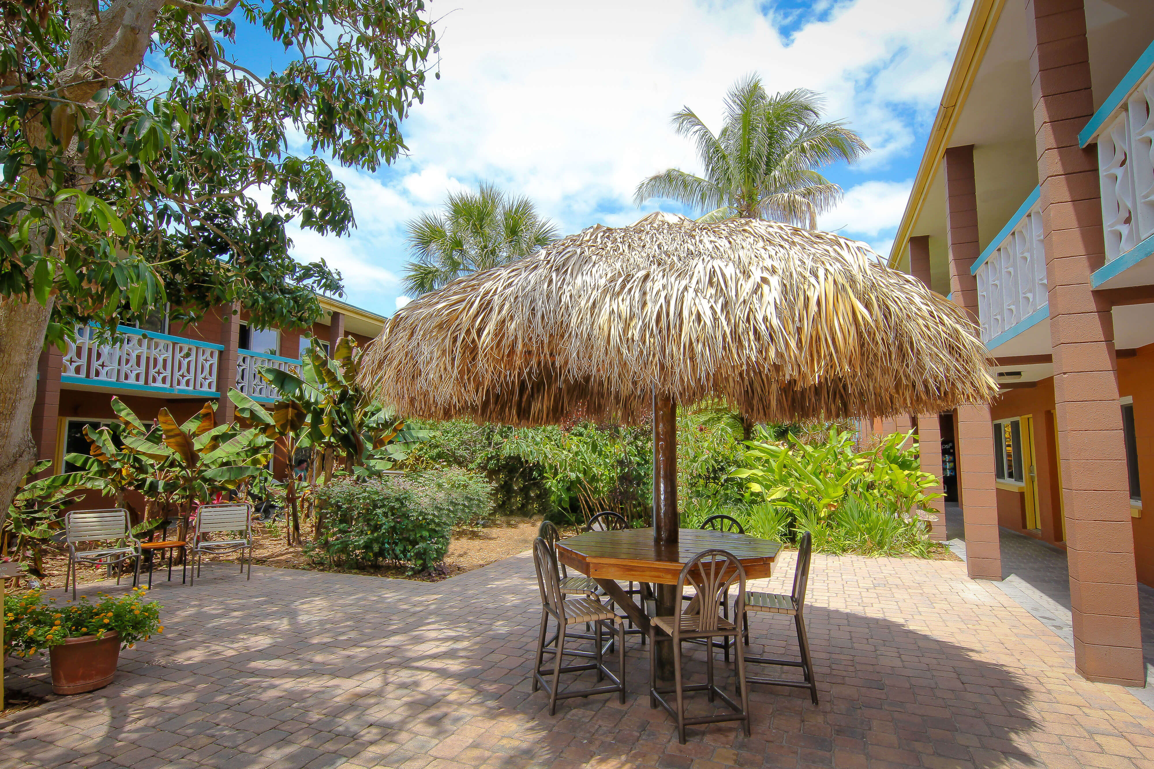 Tropically landscaped resort grounds with thatched umbrella and chairs | Wakulla Suites a Westgate Resort