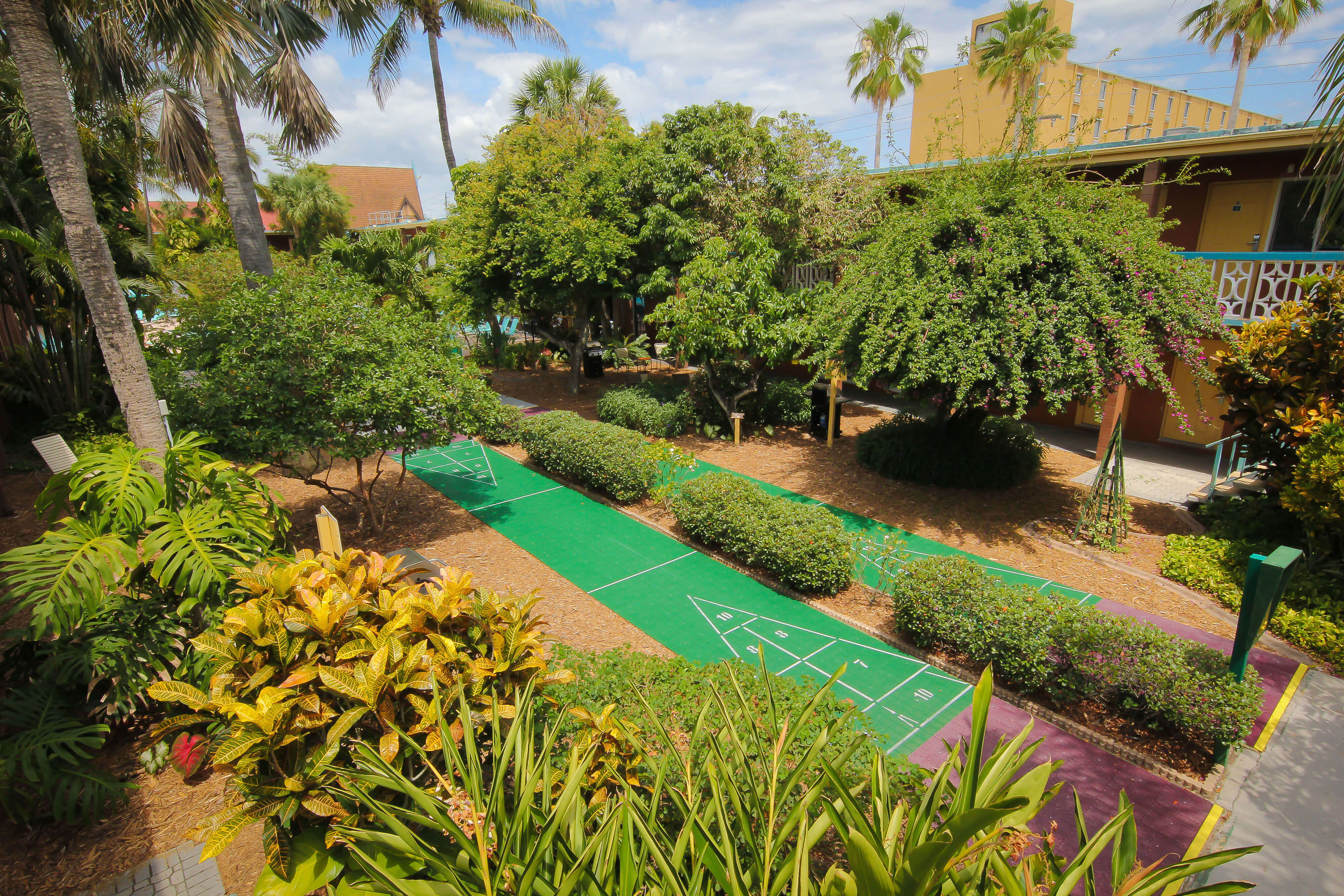 Full-size Shuffleboard Court surrounded by tropical landscaping | Wakulla Suites a Westgate Resort